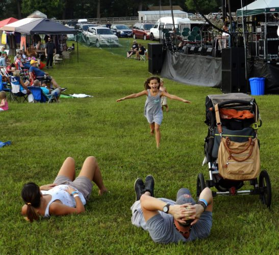 With a huge smile of joy, Lyra Lewis, 6,  runs toward her parents, Nick Lewis, right, and Jessica Diebold, left, as her little brother Grayson, 2, follows. The famly from Manassas claimed a grassy spot near the main stage at the Appaloosa Roots Music Festival on Saturday. The festival, held at Skyline Ranch Resort in Front Royal, ended Sunday night. Linda Ash/Daily